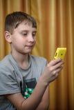 Retrato del muchacho del adolescente con el teléfono móvil en una mano Imágenes de archivo libres de regalías