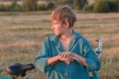 Retrato del muchacho del adolescente con la bicicleta en la puesta del sol Imagenes de archivo