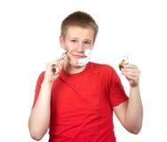 Retrato del muchacho del adolescente con la maquinilla de afeitar y un pequeño cepillo en manos Fotos de archivo libres de regalías