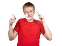 Retrato del muchacho del adolescente en una camiseta roja con la maquinilla de afeitar y de un pequeño cepillo en manos Fotografía de archivo libre de regalías