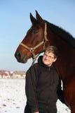 Retrato del muchacho del adolescente y del caballo de bahía en invierno Imagen de archivo