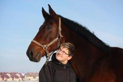 Retrato del muchacho del adolescente y del caballo de bahía en invierno Foto de archivo libre de regalías