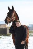 Retrato del muchacho del adolescente y del caballo de bahía en invierno Imagen de archivo libre de regalías