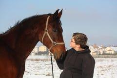 Retrato del muchacho del adolescente y del caballo de bahía en invierno Fotos de archivo libres de regalías