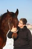 Retrato del muchacho del adolescente y del caballo de bahía en invierno Fotografía de archivo