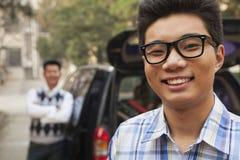 Retrato del muchacho delante del coche en campus de la universidad Imagen de archivo libre de regalías