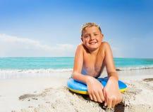 Retrato del muchacho en la playa del mar con el tablero del cuerpo Imagenes de archivo