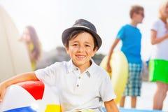 Retrato del muchacho en la playa y sus amigos Foto de archivo libre de regalías