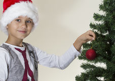 Retrato del muchacho feliz en el casquillo de Papá Noel que adorna el árbol de navidad Fotografía de archivo libre de regalías