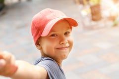 Retrato del muchacho feliz en el casquillo que sostiene la sonrisa y llevar a cabo la mano imagen de archivo libre de regalías