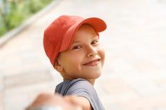 Retrato del muchacho feliz en el casquillo que sostiene la sonrisa y llevar a cabo la mano fotos de archivo libres de regalías