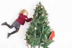 Retrato del muchacho feliz que adorna el árbol de navidad, vestido en suéter Imagen de archivo