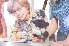 Retrato del muchacho hermoso mientras que hace notas Fotografía de archivo libre de regalías