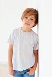Retrato del muchacho joven hermoso, niño que presenta cerca de la pared blanca imagen de archivo