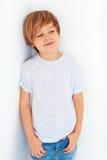 Retrato del muchacho joven hermoso, niño que presenta cerca de la pared blanca imagen de archivo libre de regalías
