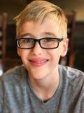 Retrato del muchacho joven sonriente en vidrios Imágenes de archivo libres de regalías