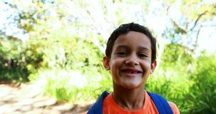 Retrato del muchacho lindo con la cartera que se coloca en parque almacen de metraje de vídeo