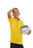 Retrato del muchacho lindo con un balón de fútbol aislado en un fondo blanco Adolescente atlético en camisa amarilla y pantalones Foto de archivo libre de regalías
