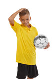 Retrato del muchacho lindo con un balón de fútbol aislado en un fondo blanco Adolescente atlético en camisa amarilla y pantalones Foto de archivo