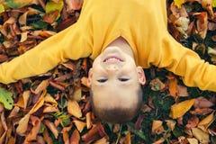 Retrato del muchacho lindo feliz con el fondo de las hojas de otoño Fotos de archivo