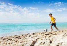 Retrato del muchacho lindo que juega a fútbol en la playa Imagen de archivo