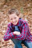 Retrato del muchacho lindo que se sienta en hojas con encendido una rodilla Foto de archivo libre de regalías