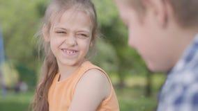 Retrato del muchacho lindo y de la muchacha que se sientan en el parque, hablando y divirtiéndose Un par de niños felices Despreo almacen de metraje de vídeo