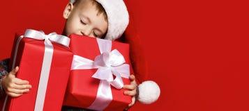 Retrato del muchacho pensativo en el sombrero de Papá Noel en fondo rojo imagen de archivo