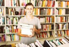 Retrato del muchacho positivo del adolescente con la pila del libro Fotografía de archivo