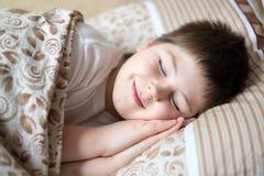 Retrato del muchacho que duerme en día de la cama Fotos de archivo
