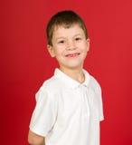 Retrato del muchacho que hace muecas en rojo Foto de archivo