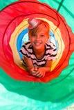 Retrato del muchacho que miente en túnel de la tienda Fotos de archivo