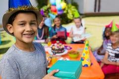 Retrato del muchacho que muestra la caja de regalo Imagen de archivo