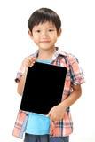 Retrato del muchacho que se coloca con la tableta Fotografía de archivo
