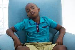 Retrato del muchacho que se sienta en la butaca azul en casa fotos de archivo