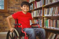 Retrato del muchacho que se sienta en silla de ruedas en la biblioteca Foto de archivo