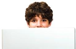 Retrato del muchacho que usa una computadora portátil Fotos de archivo