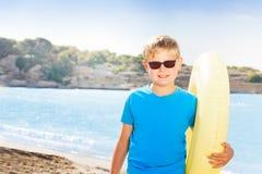 Retrato del muchacho rubio en gafas de sol en la playa arenosa Imagenes de archivo