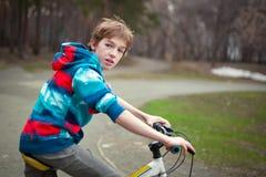 Retrato del muchacho serio con la bicicleta en parque Fotografía de archivo