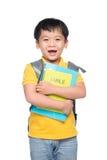 Retrato del muchacho sonriente lindo con la mochila y los libros coloridos, e Foto de archivo