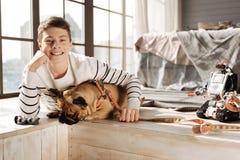 Retrato del muchacho sonriente mientras que abraza su perro Imagen de archivo