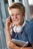 Retrato del muchacho sonriente que habla en el teléfono elegante. Fotografía de archivo
