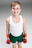 Retrato del muchacho sonriente que lleva a cabo pesas de gimnasia imagen de archivo libre de regalías
