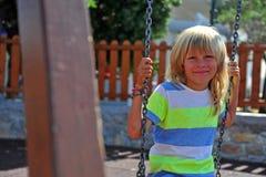 Retrato del muchacho sonriente que se sienta en el oscilación Fotos de archivo libres de regalías