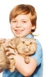 Retrato del muchacho sonriente que sostiene el gato grande Imagen de archivo