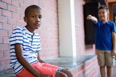 Retrato del muchacho triste en pasillo de la escuela Imagen de archivo libre de regalías