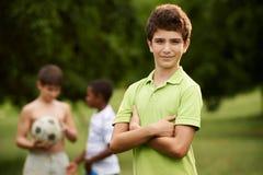 Retrato del muchacho y de los amigos que juegan a fútbol en parque imagenes de archivo