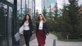 Retrato del negocio de dos mujeres jovenes en el fondo de un edificio moderno las mujeres de negocios caminan con confianza a lo  almacen de metraje de vídeo
