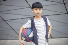 Retrato del niño asiático fresco que lleva a cabo baloncesto al aire libre Foto de archivo
