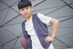 Retrato del niño asiático fresco que lleva a cabo baloncesto al aire libre Fotos de archivo